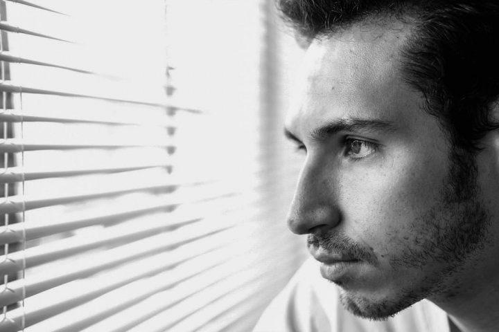 man peeking through a window blind