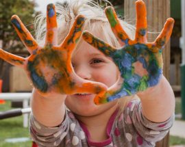 child smiling with paint in her hands