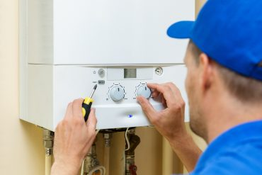 man installing a hot water cylinder